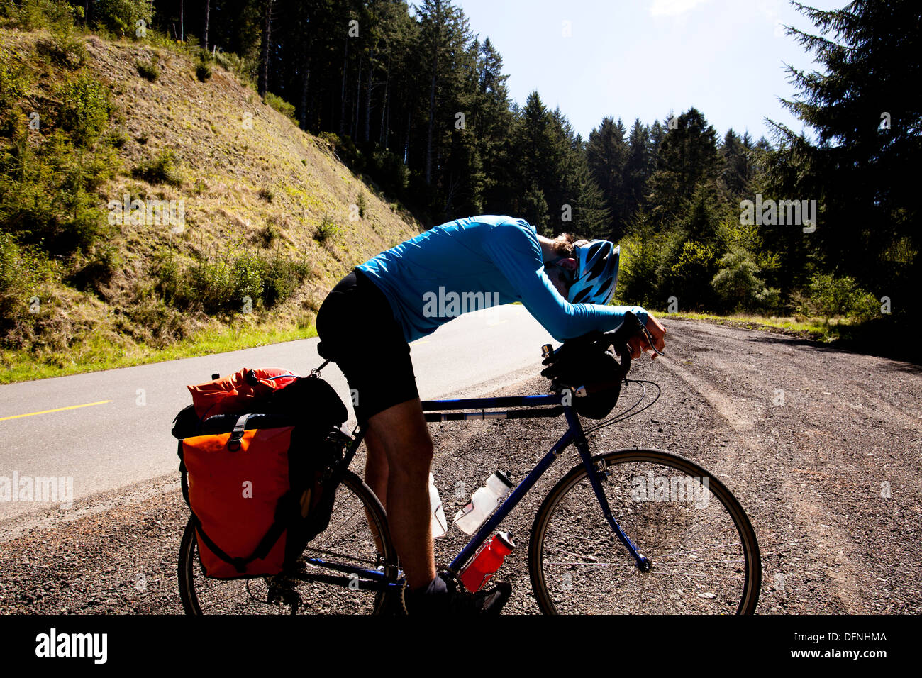 An exhausted male cyclist leans over his touring bike while climbing Mattole Road near Ferndale, California. - Stock Image