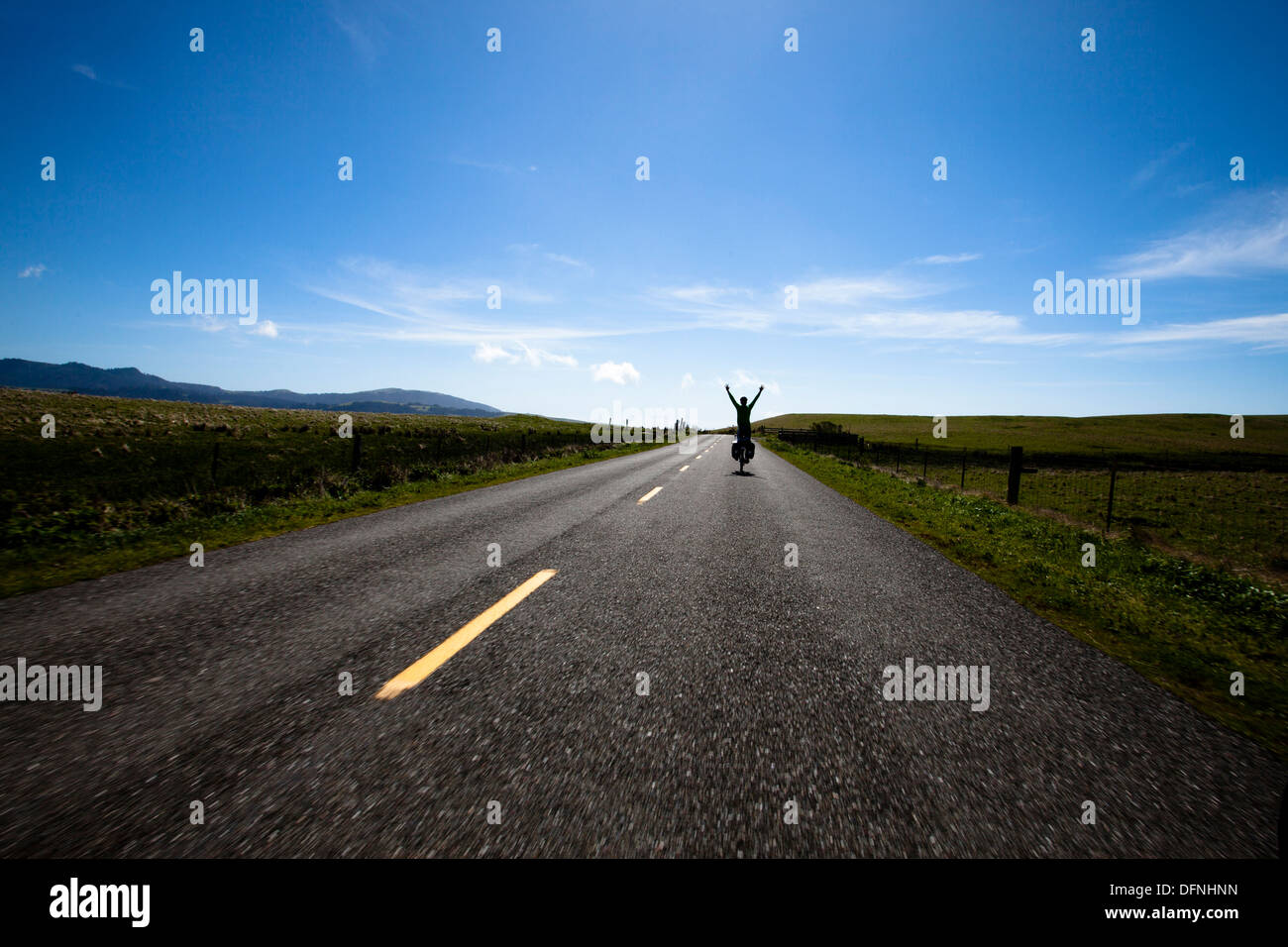 A male cyclist raises his arms above his head after reaching the summit of Mattole Road near Ferndale, California. - Stock Image