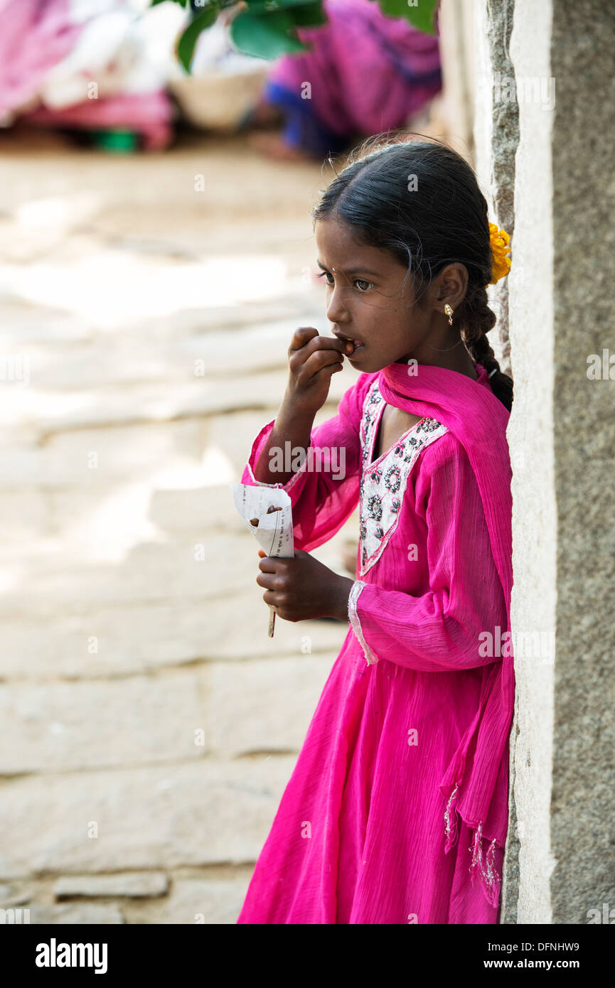 Young Indian girl standing eating peanuts in a rural indian village. Andhra Pradesh, India - Stock Image