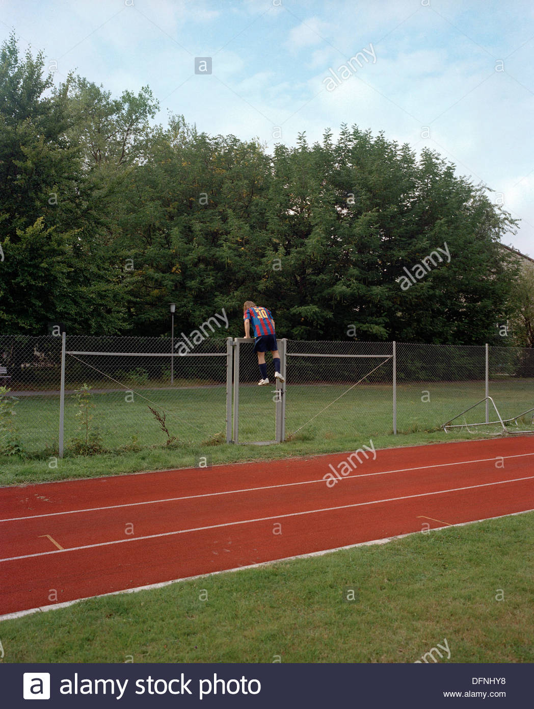 Leisure footballer dressed in Messi shirt climbs over a fence to get a ball, Munich, Upper Bavaria, Bavaria, Germany - Stock Image