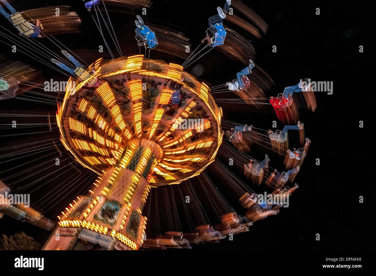 kids go for a whirl .A night motion image of an amusement park ride in operation. - Stock Image