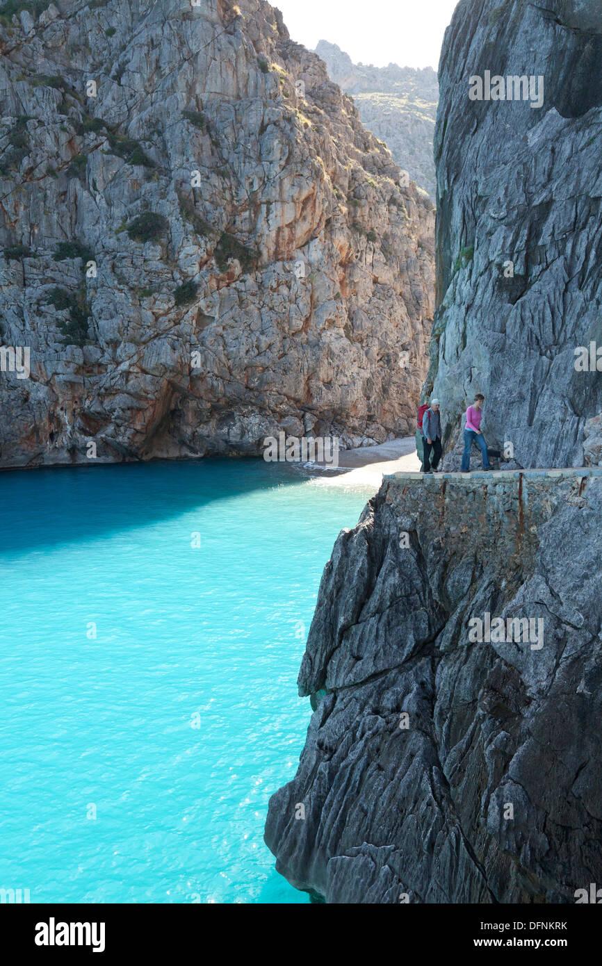 Hikers above the bay of Sa Calobra, Cala de Sa Calobra, end of the canyon Torrent de Pareis, romantic beach, Serra de Tramuntana - Stock Image