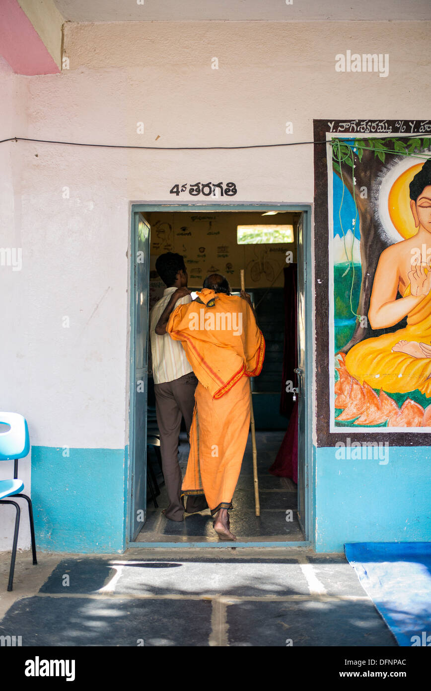 Old Indian sadhu being helped into the Sri Sathya Sai Baba mobile outreach hospital clinic. Andhra Pradesh, India - Stock Image