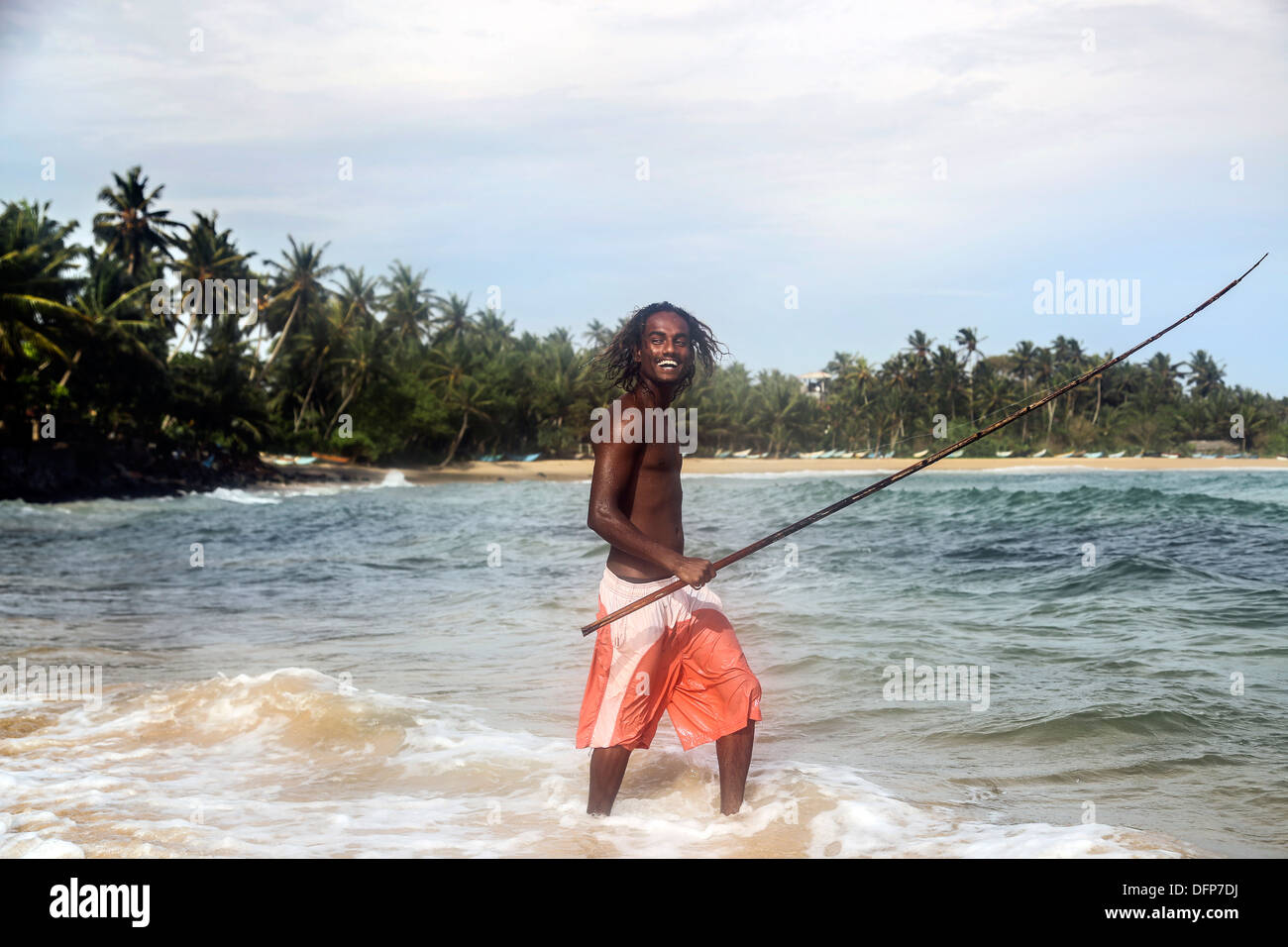 Fishman paddles with rod in sea smiling shorts - Stock Image