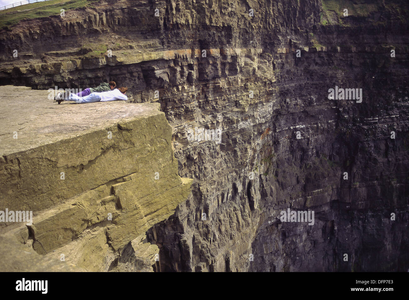 Two people lie precariously on the edge of great slab overlooking the Cliffs of Moher near Lahinch. Co. Clare, Ireland - Stock Image