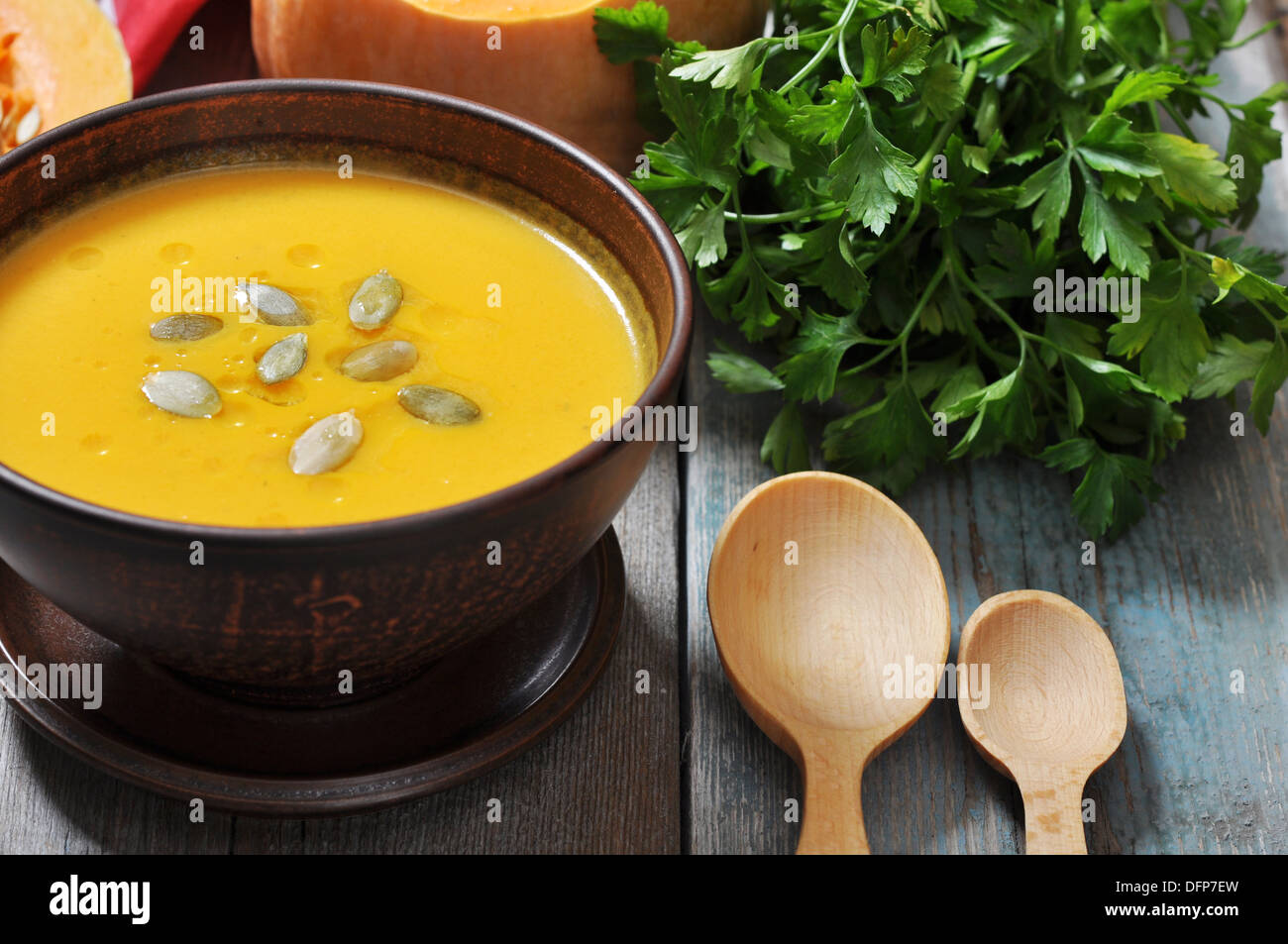 Bowl of pumpkin soup on rustic wooden table. - Stock Image