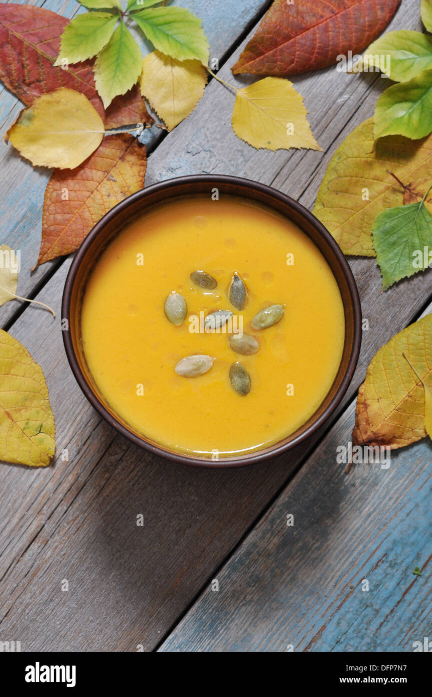 Bowl of pumpkin soup on rustic wooden table. Stock Photo