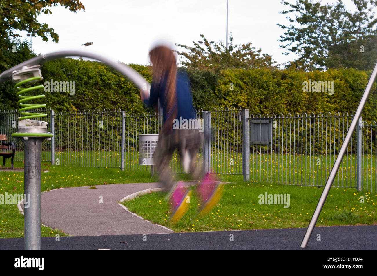 Little Girl bouncing on a Seesaw at a childrens playground with subject movement blur - Stock Image