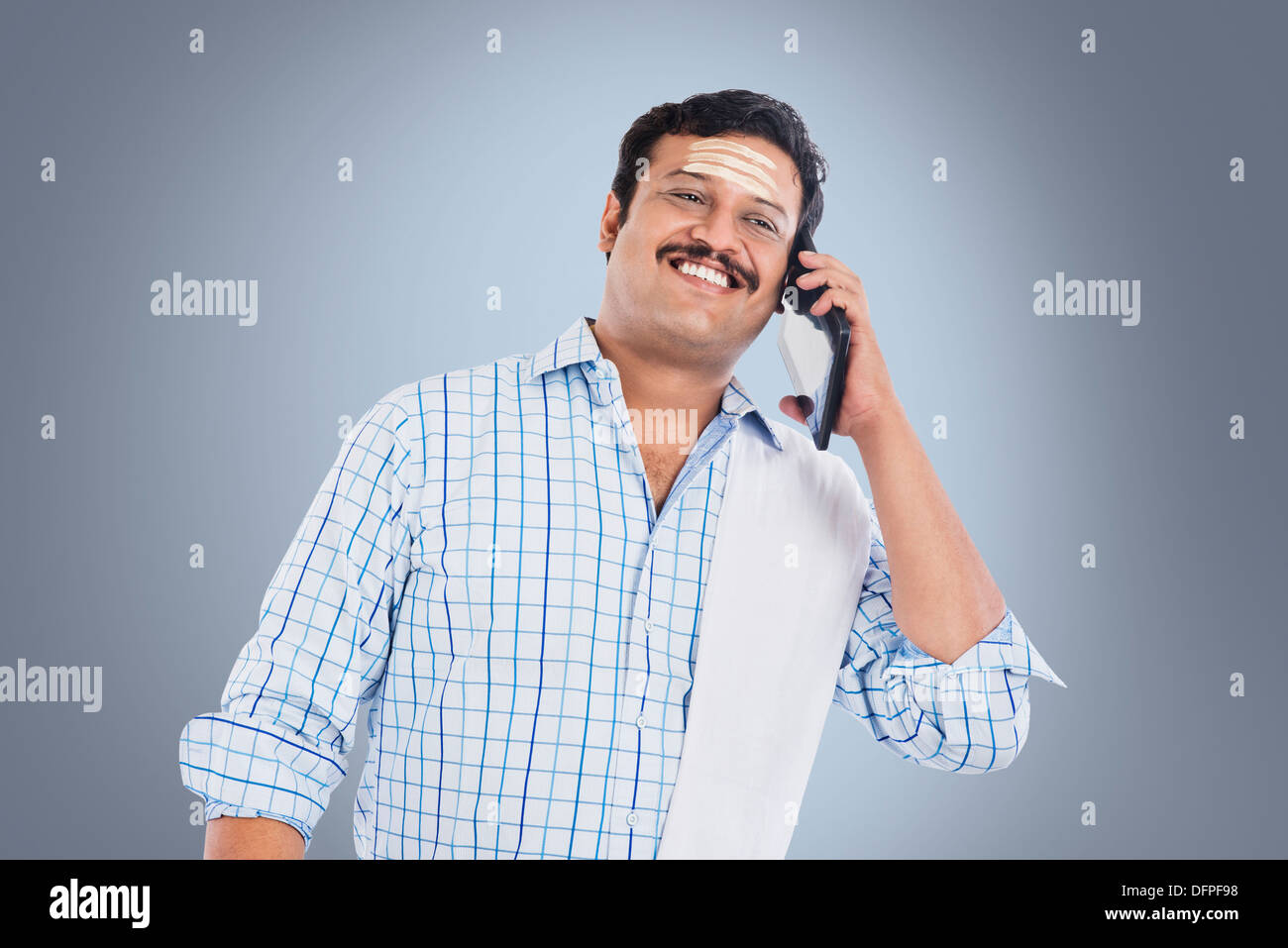 South Indian man talking on a mobile phone and smiling Stock Photo