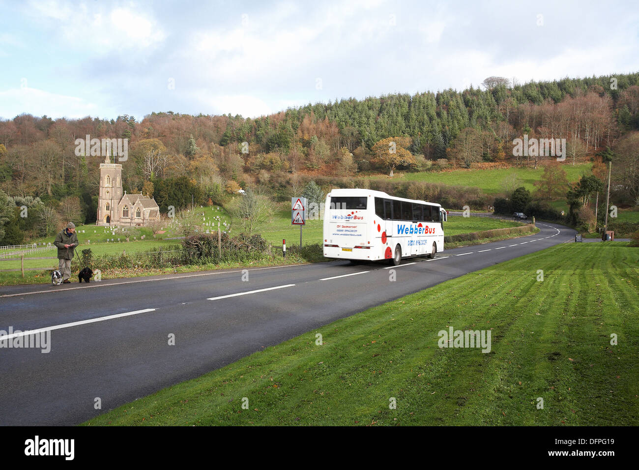 A Webber coach traveling along the A39 at west Quantoxhead, Somerset in England with Saint Etheldreda's Church in the distance. - Stock Image