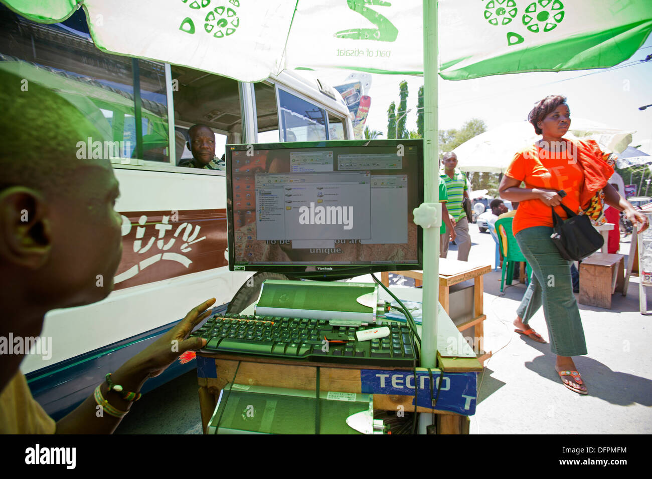 Street stall under a parasol with a desktop computer selling illegal MP3 music downloads, Kariakoo, Dar es Salaam, - Stock Image