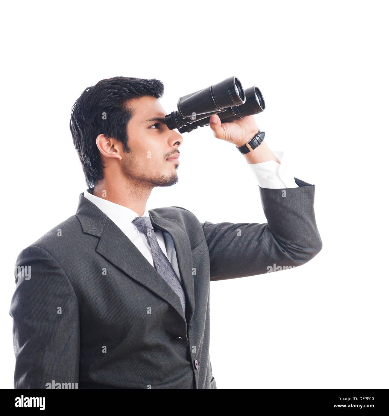 Businessman looking through binoculars - Stock Image