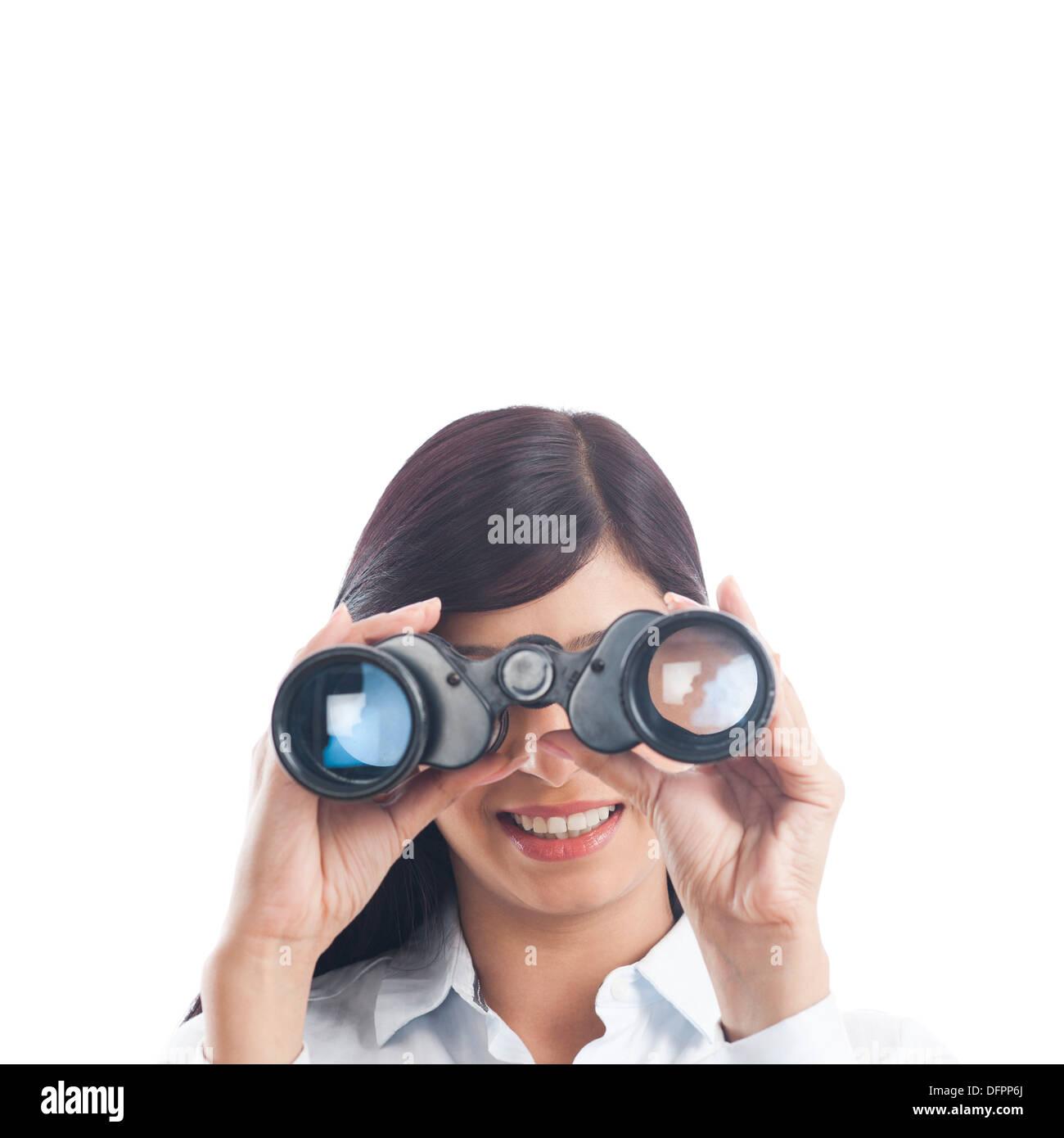 Businesswoman looking through binoculars - Stock Image