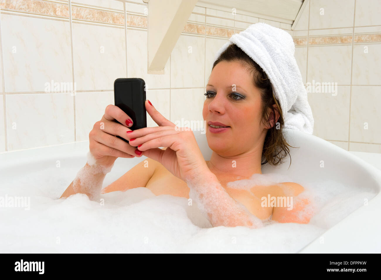 A woman is playing with her smartphone while she is enjoying a hot bath - Stock Image