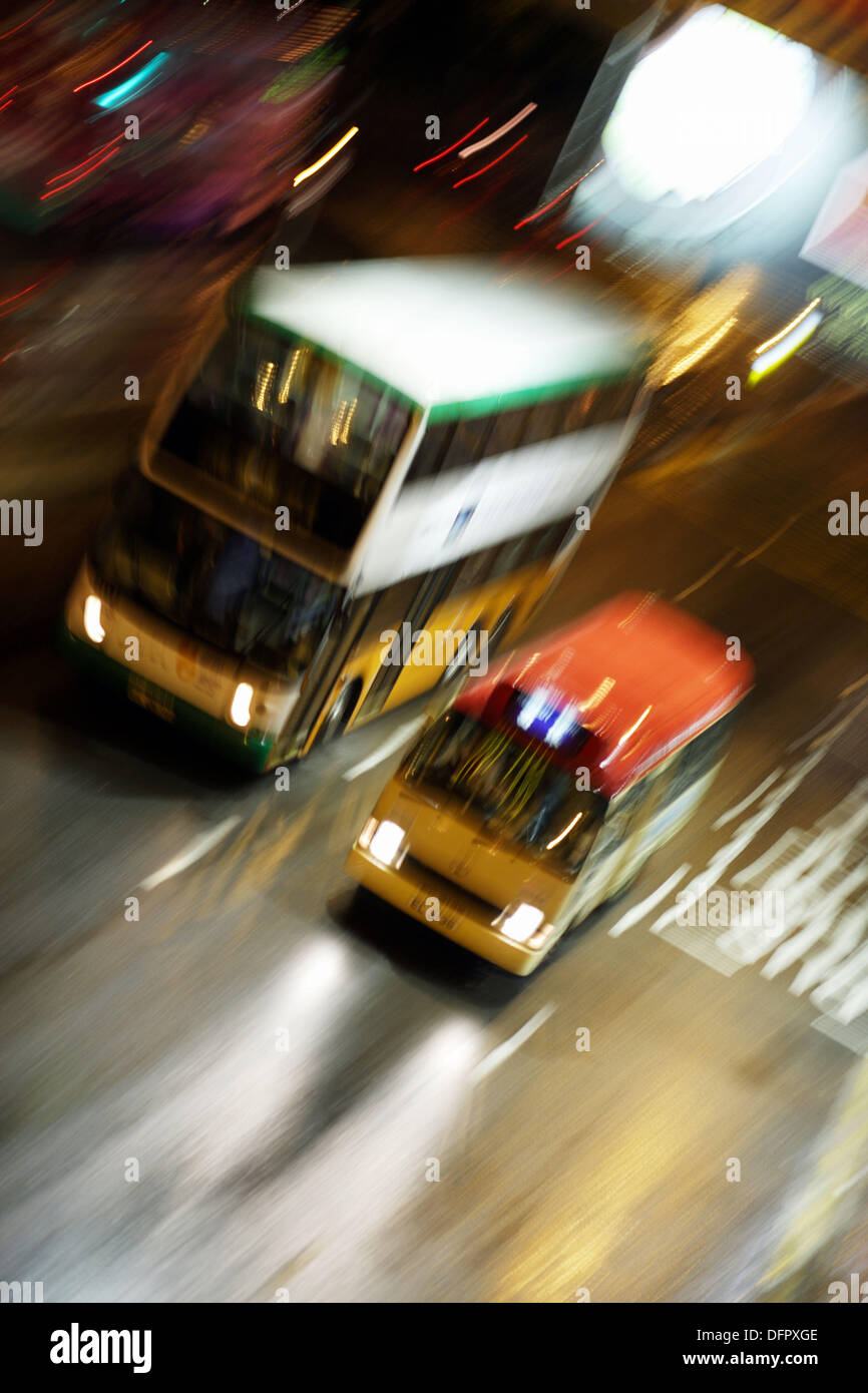 Two public busses, one typical doubledecker and one minibus, besides each other moving in high speed on a wet street in Wanchai - Stock Image