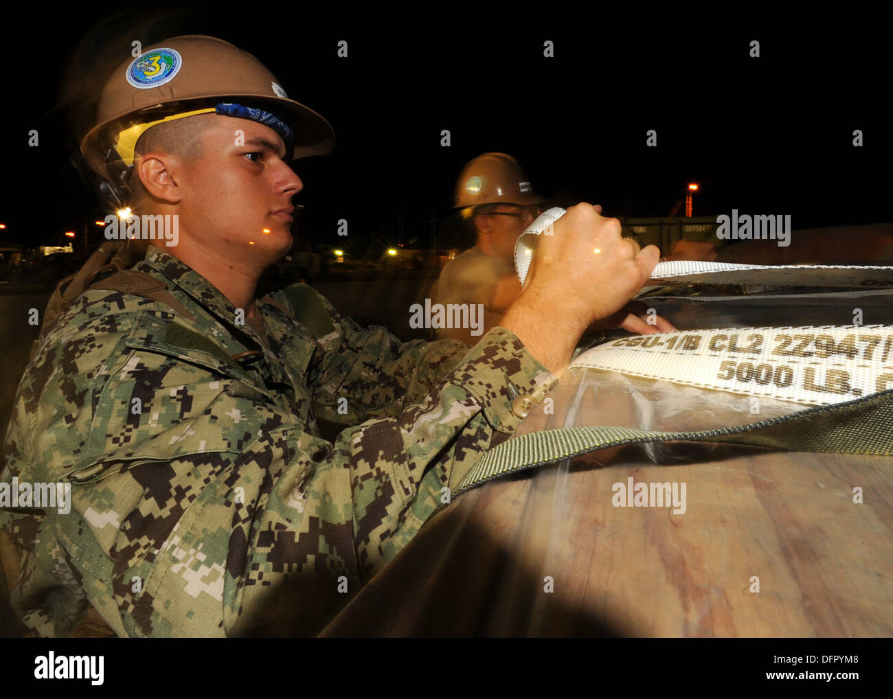 Construction Electrician 3rd Class Jonathan Buckwalter, assigned to Naval Mobile Construction Battalion (NMCB) 3, tightens pull- - Stock Image