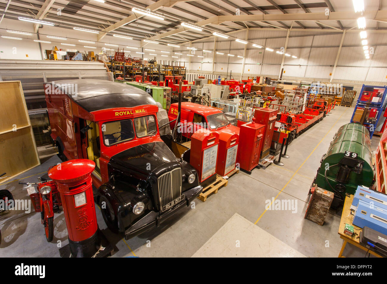 Objects stored at the British Postal Museum Store at Debden. A Morris Commercial LC5 Royal Mail van from 1956 sits in the foreground with a line of private posting boxes. Mail cars from the Post Office (London) Railway from 1927-1930 can be seen in the midground. - Stock Image
