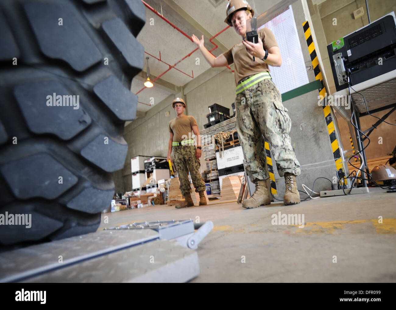 Equipment Operator 2nd Class Jennifer Harris, assigned to Naval Mobile Construction Battalion (NMCB) 3, guides a medium tactical - Stock Image