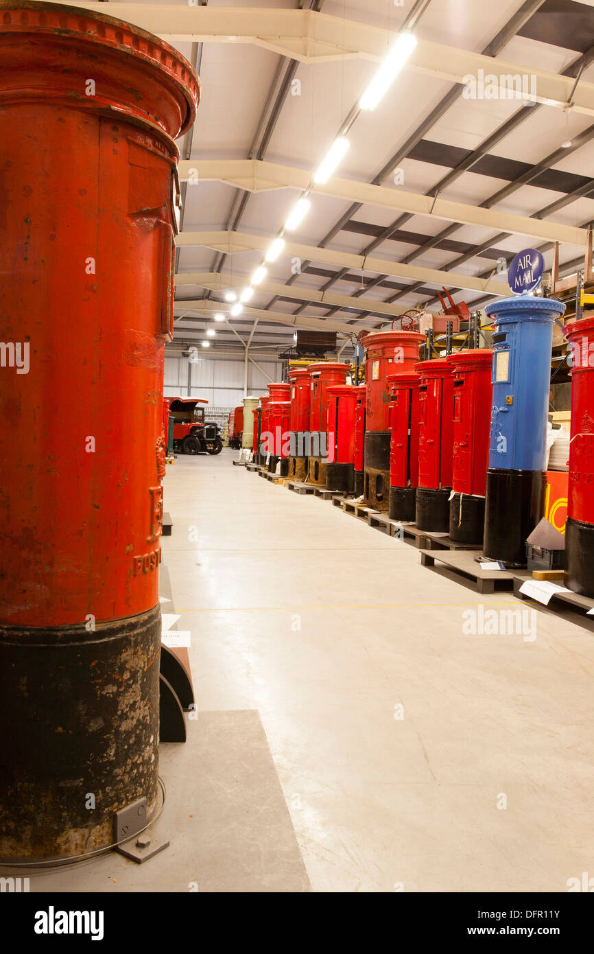 The line of pillar boxes at the British Postal Museum Store at Debden. The blue pillar box is a restored example of a box from the 1930s, which were intended for the collection of air mail. - Stock Image