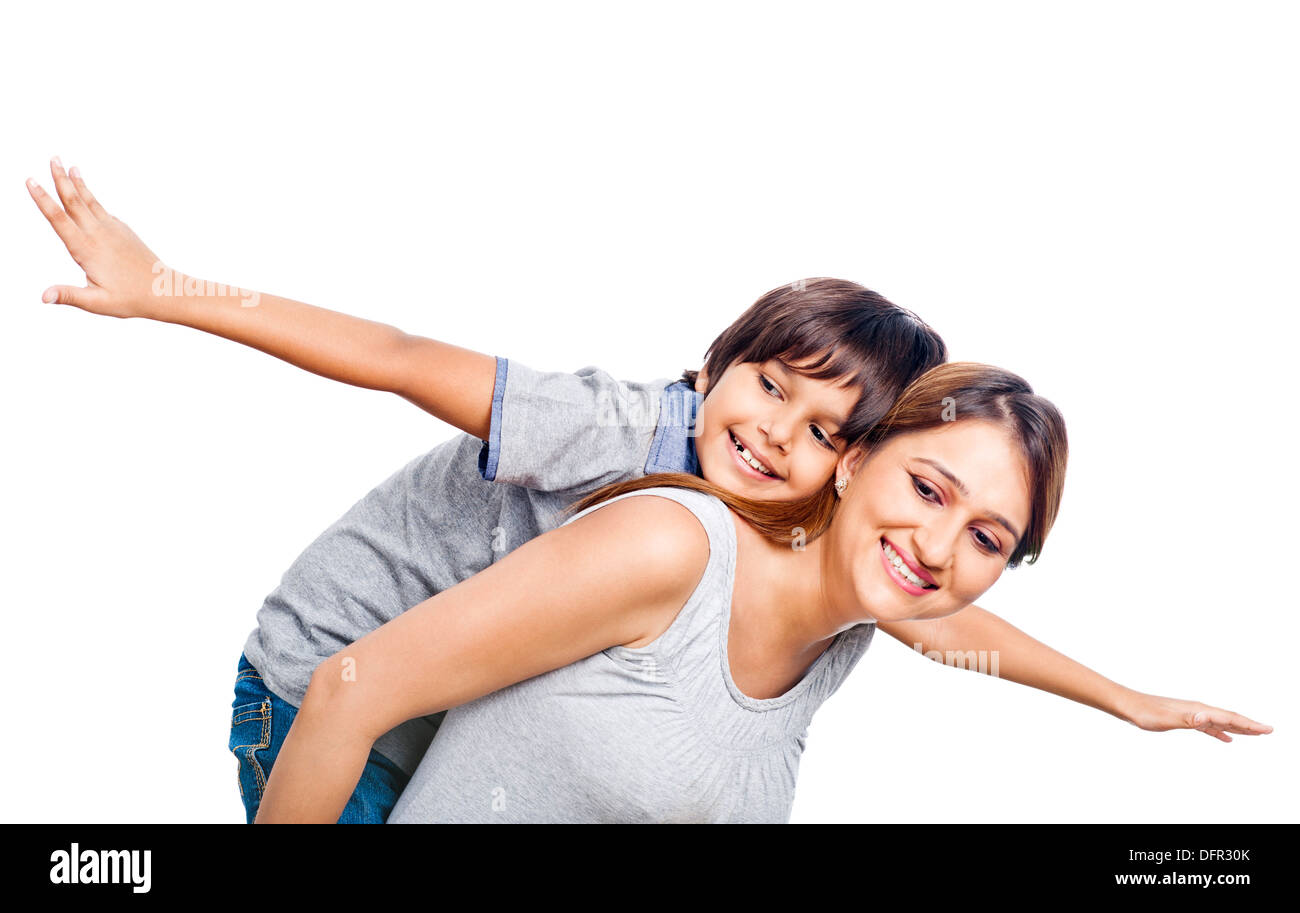 Boy riding piggyback on his mother - Stock Image