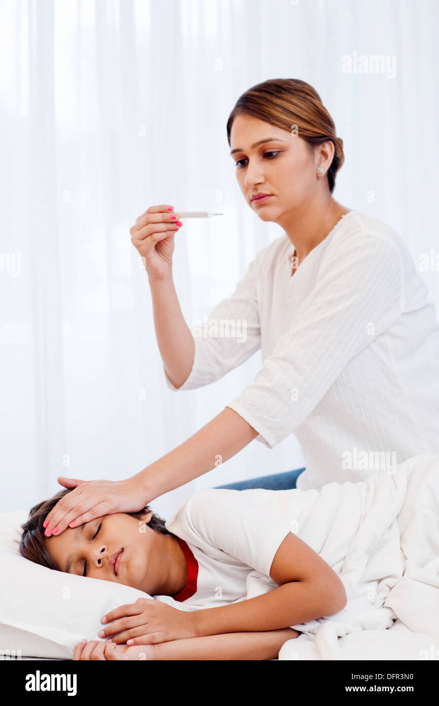 Woman checking fever of her son with a thermometer - Stock Image
