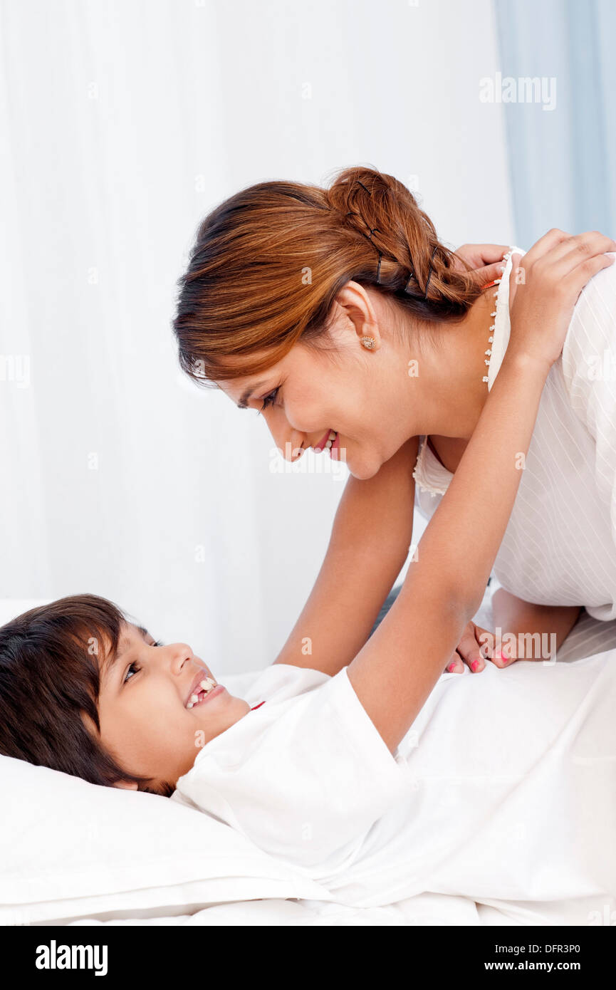 Boy hugging his mother on the bed - Stock Image