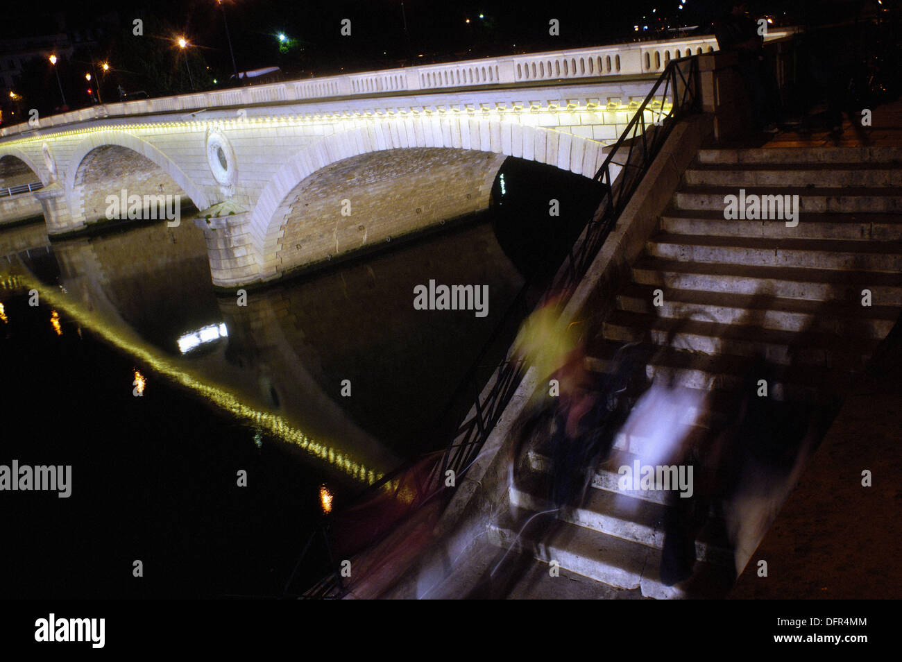 People on steps near Pont Louis-Philippe at night. Paris. France - Stock Image