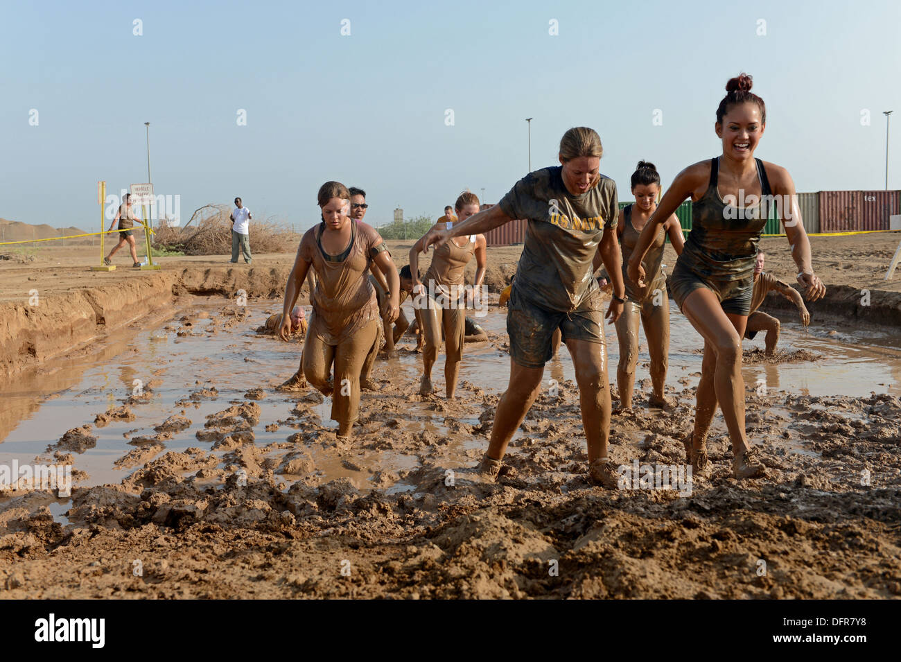 Service members and civilians compete in a Mud Run on Camp Lemonnier. - Stock Image