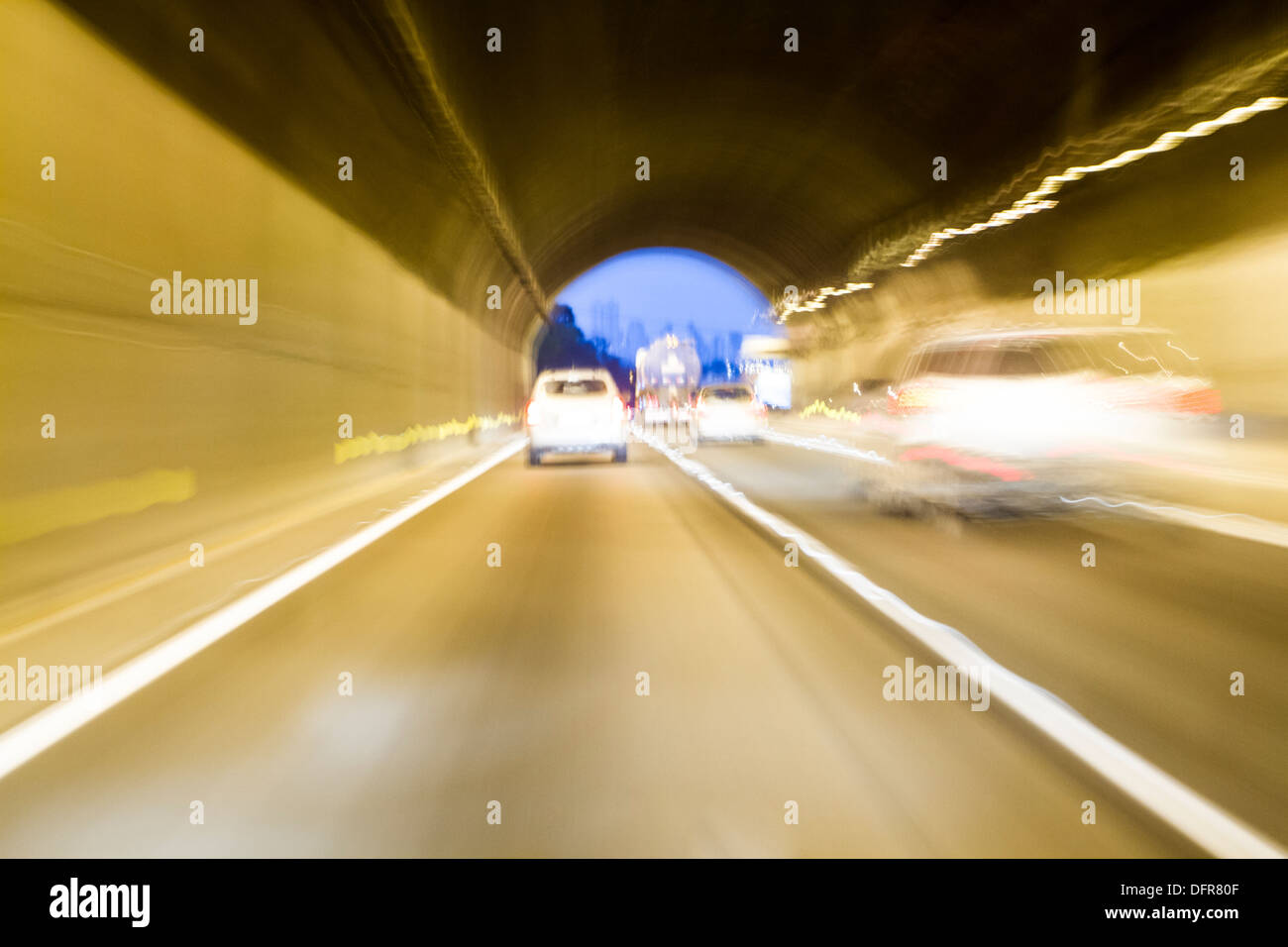Blurred motion on a road tunnel at evening. - Stock Image