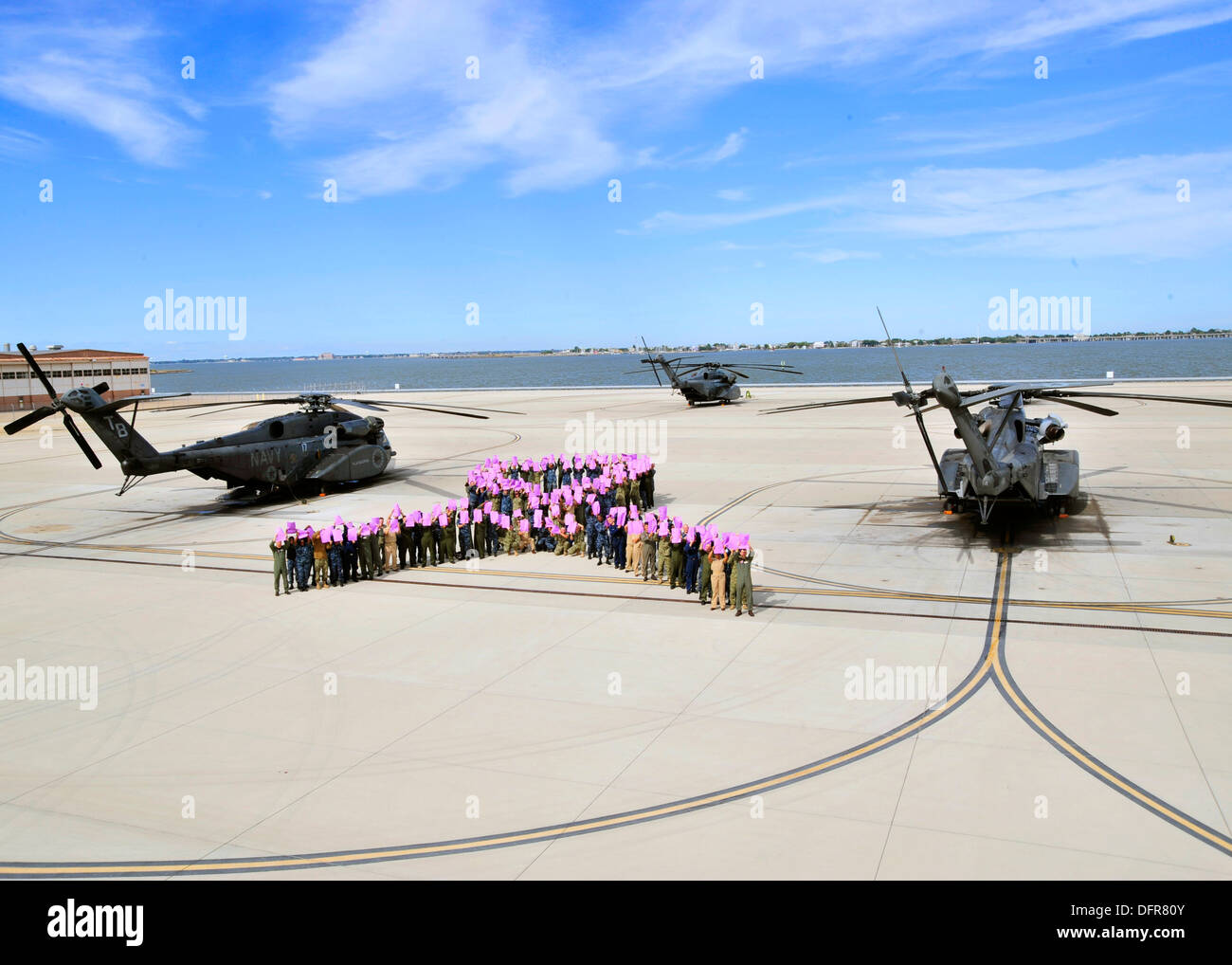 Sailors and civilians attached to Helicopter Mine Countermeasures Squadron (HM) 15 'Blackhawks,' form a human ribbon in support - Stock Image