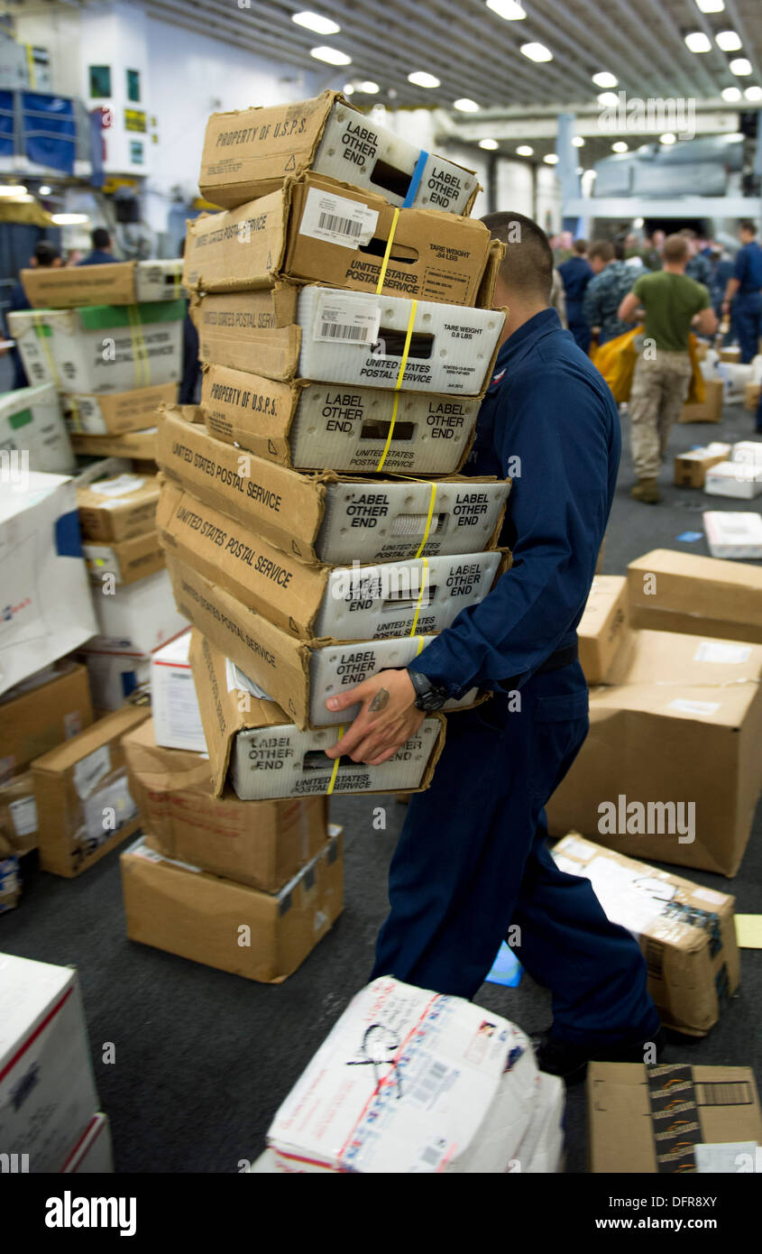 Ship's Serviceman 2nd Class Sergio Gomez moves packages of mail aboard the amphibious assault ship USS Boxer (LHD 4). Boxer is - Stock Image