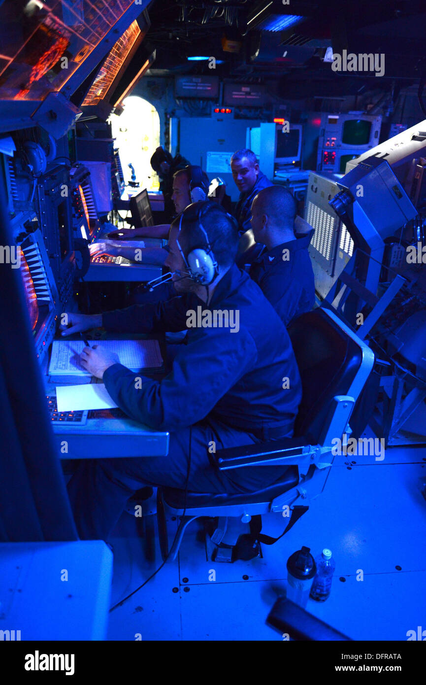 Sailors assigned to the combat information center aboard the Arleigh Burke-class guided-missile destroyer USS Ramage (DDG 61) analyze signatures to aid in tactical control of the ship. Ramage, home-ported in Norfolk, Va., is on a scheduled deployment supp - Stock Image