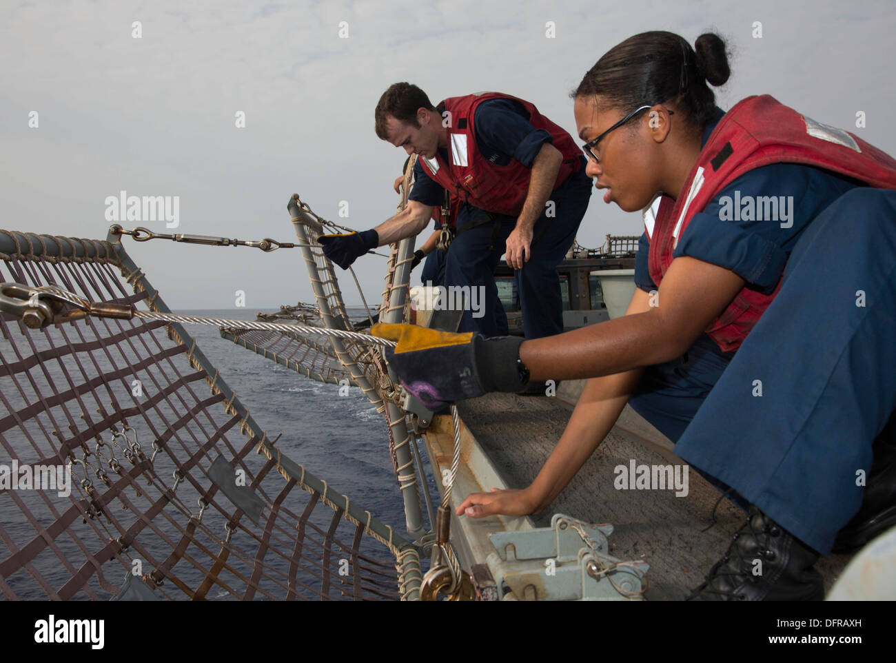 Ship's Serviceman Seaman Marcia Puello, right, and Hull Technician 2nd Class Sean Roberts lower safety nets prior to flight operations aboard the guided-missile destroyer USS Mason (DDG 87). Mason is deployed in support of maritime security operations and - Stock Image