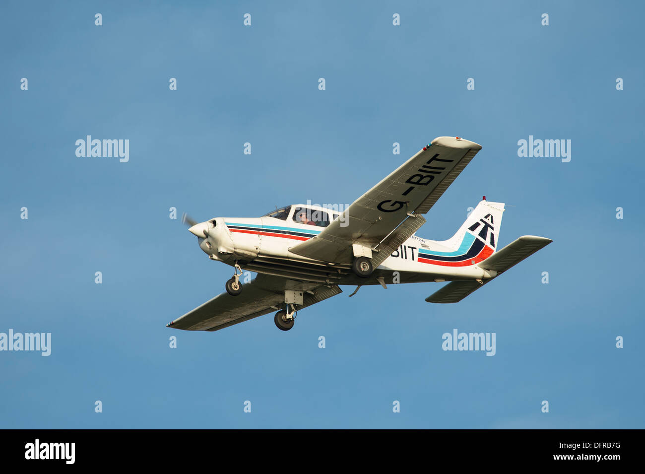 Light aircraft in Tayside Aviation colours flying overhead on a summer's day. - Stock Image
