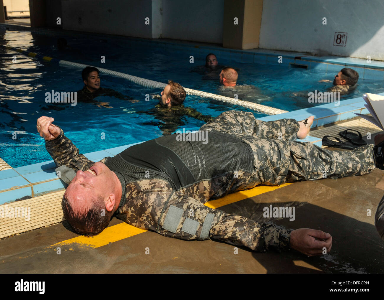 Army Lt. Col. John Warner lies on the ground after completing a relay swim race. Competitors swam one lap of the pool while wea - Stock Image