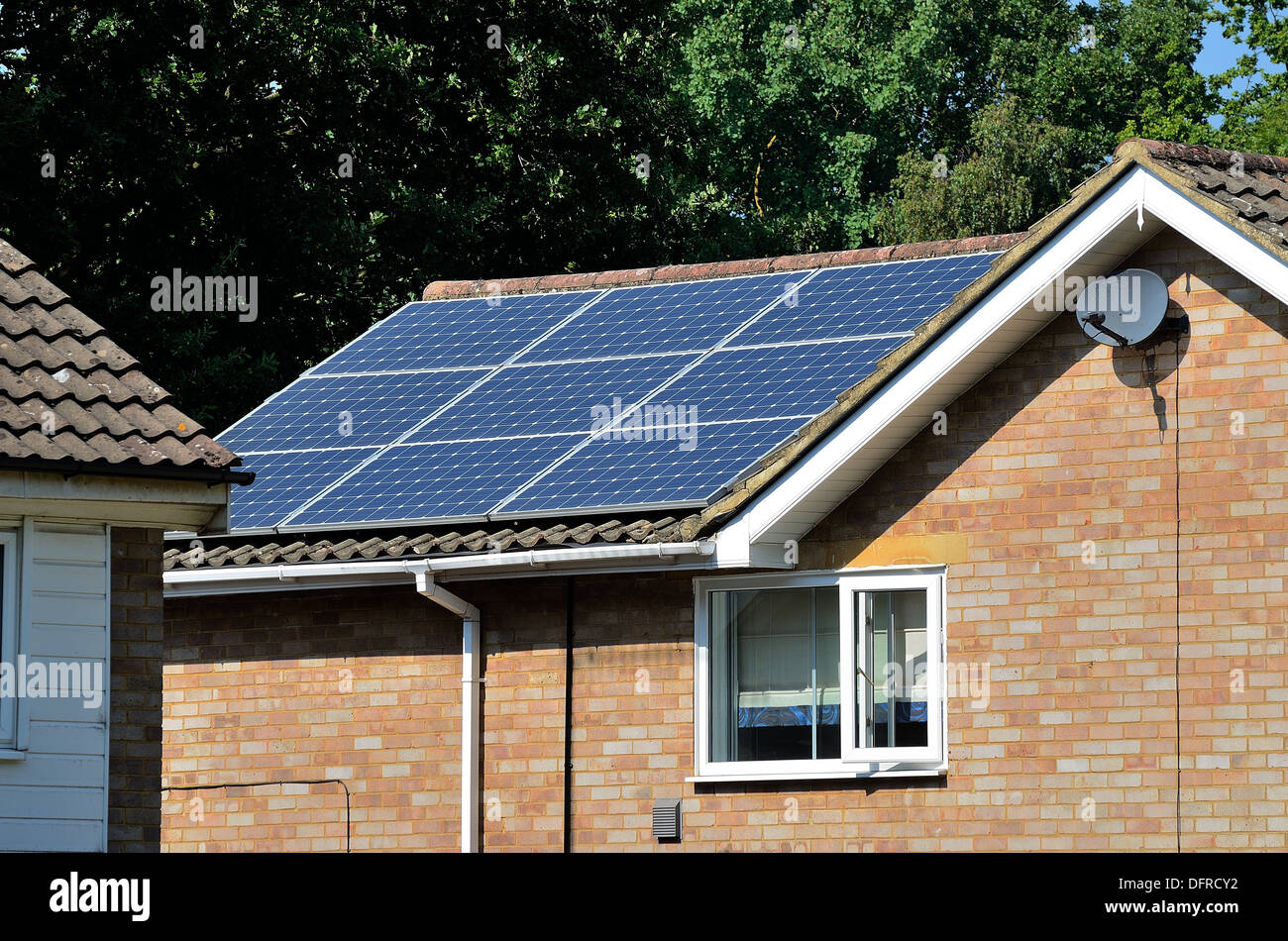 Suburban house with solar panels on roof - Stock Image