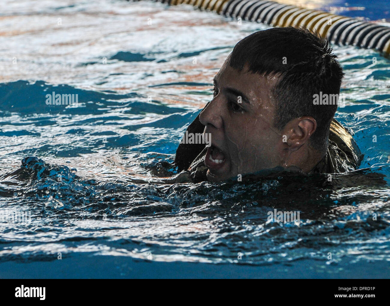 Navy Hospital Corpsman 3rd Class Javier Uvina swims during a relay swim race. Competitors swam one lap of the pool while wearin - Stock Image
