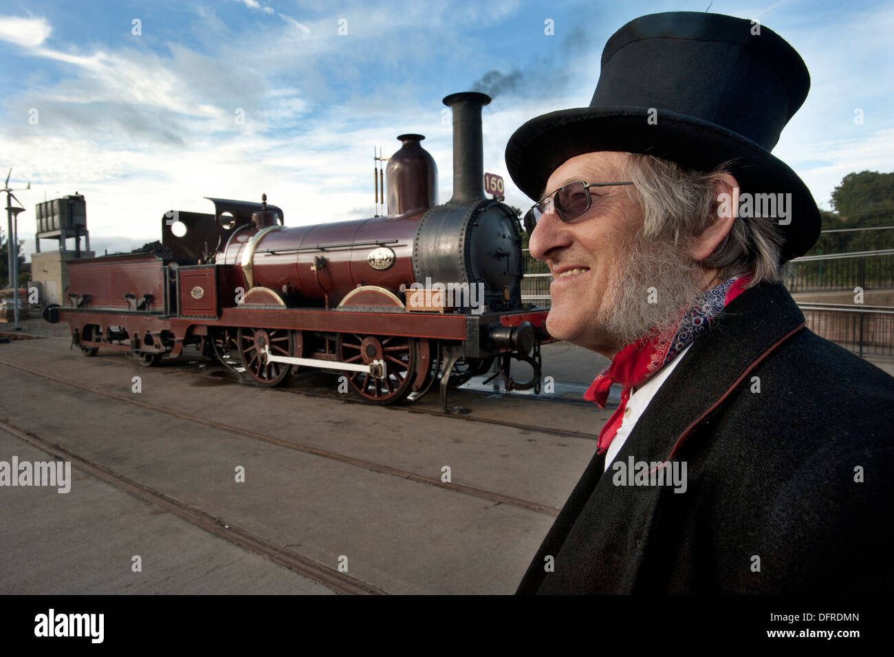 A Period dressed driver Alan Middleton wearing a Top Hat by his steam locomotive Furness Railway number 20, Britains oldest working standard gauge steam locomotive, at the National Railway Museums Shildon museum - Stock Image