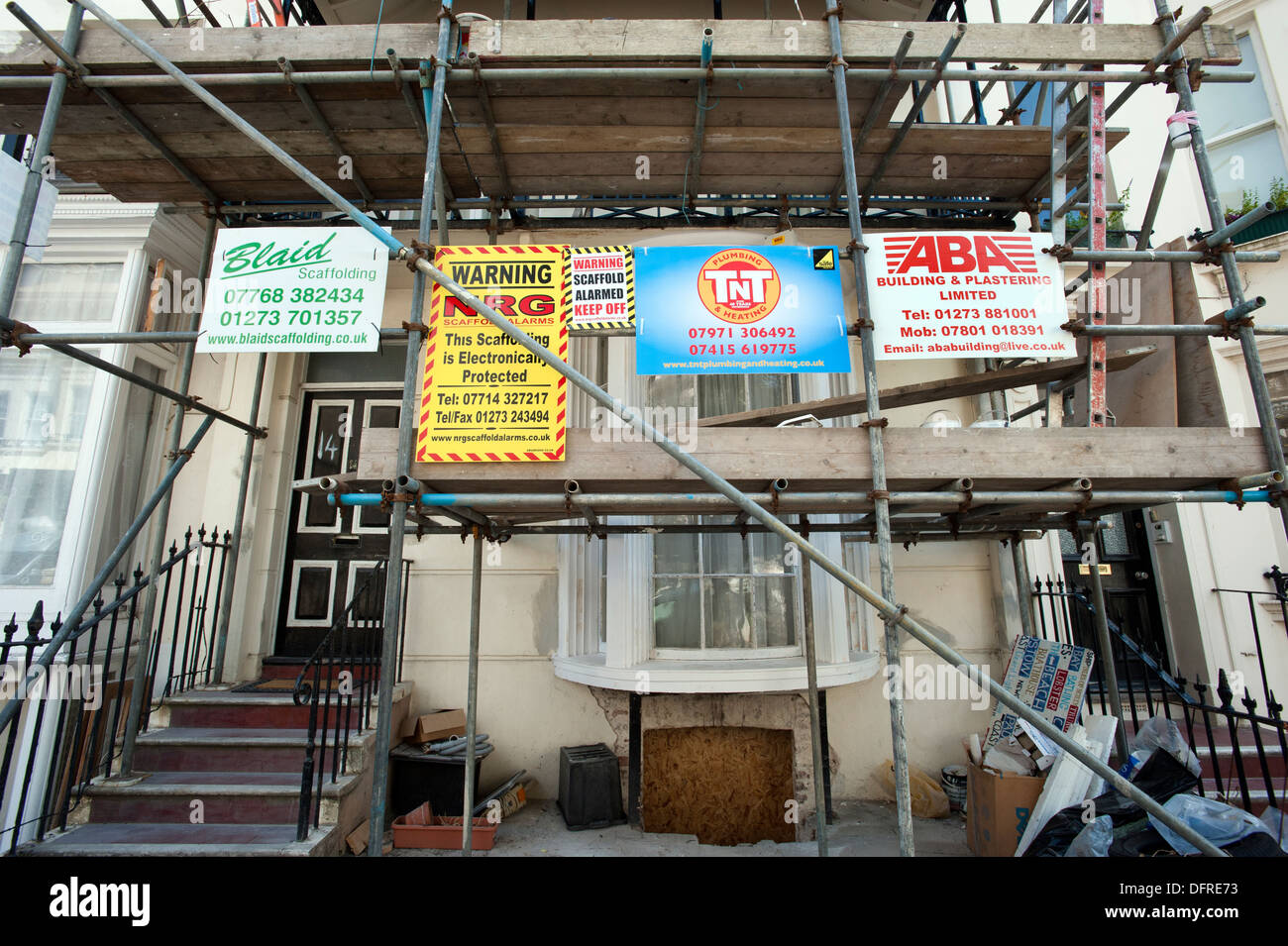 Builders' advertising boards on scaffolding on an 1822 built Regency house under restoration in central Brighton. - Stock Image