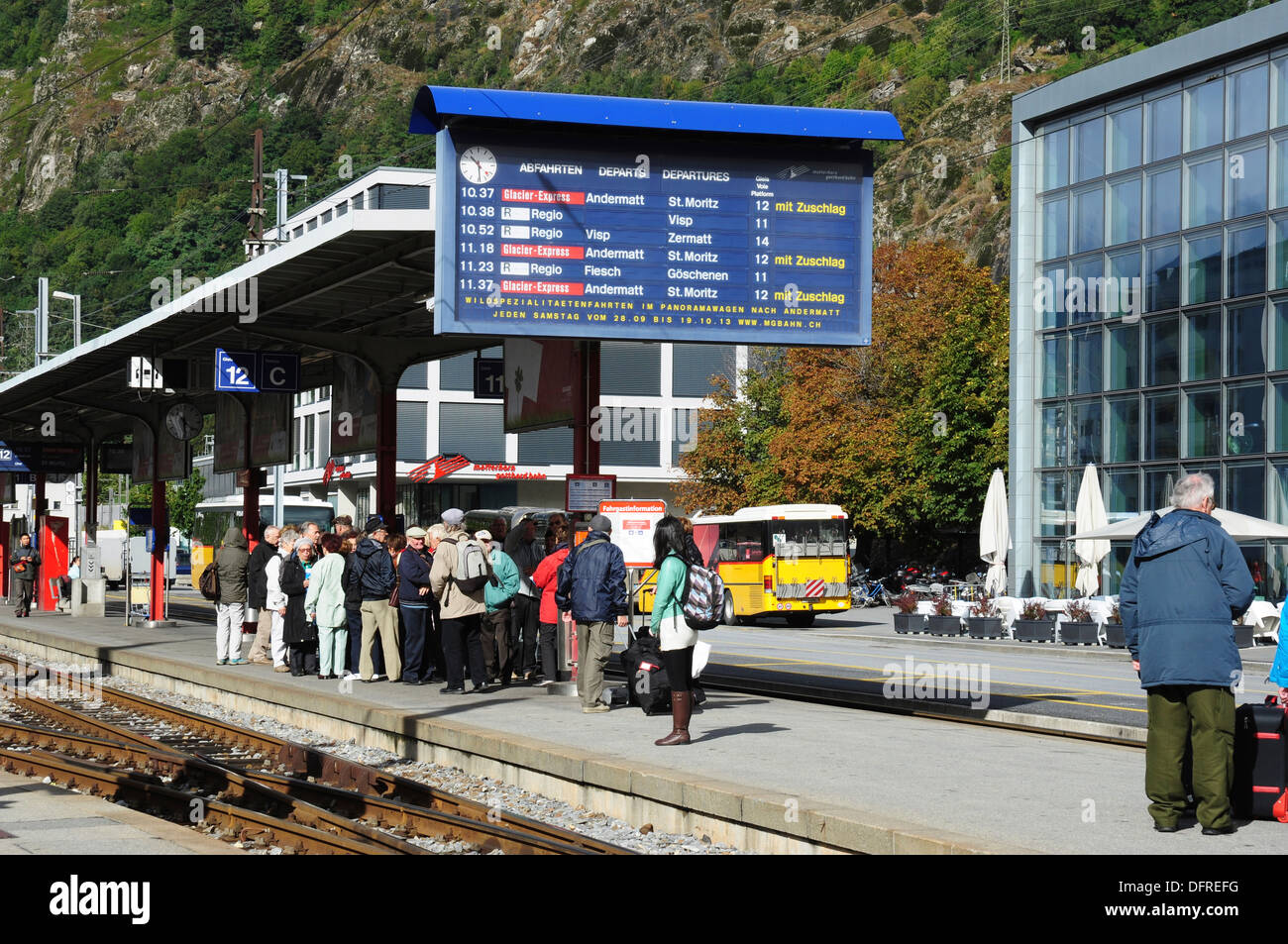 Passengers and train departure information board at Brig railway station, Valais, Switzerland - Stock Image
