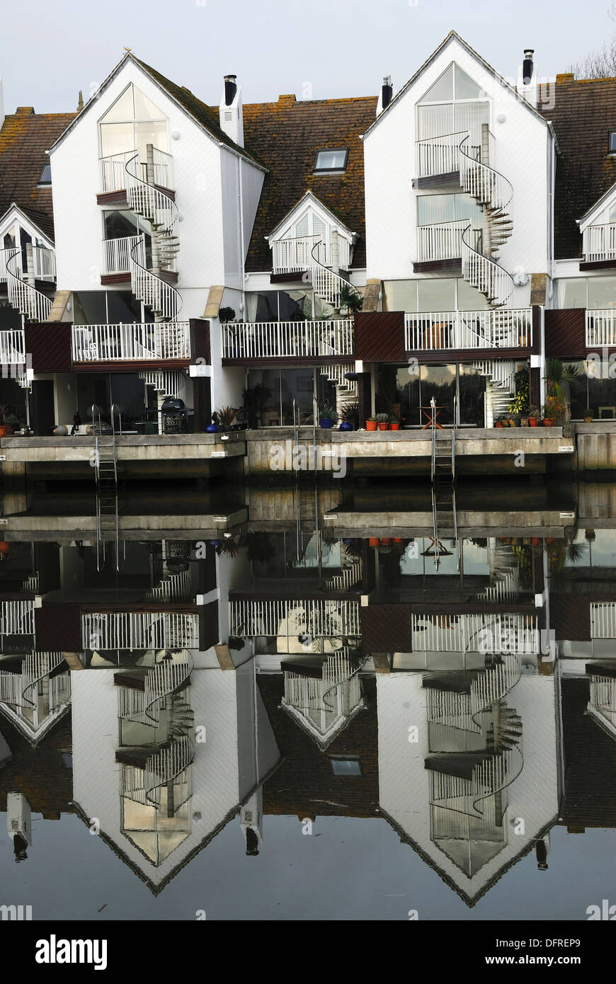 Houses with their reflections on Christchurch harbour Dorset UK - Stock Image