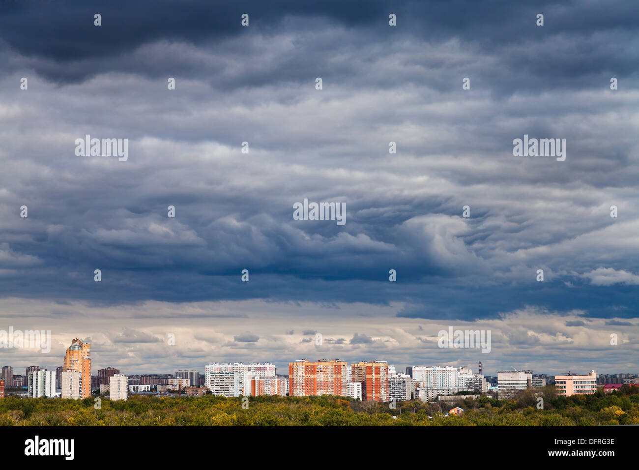 skyline with dark blue storm clouds over city in autumn - Stock Image