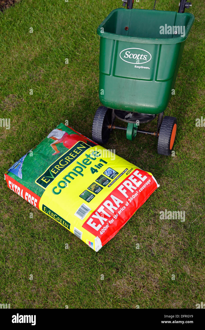 Evergreen Complete 4 in 1 summer grass food and a Scott's Easygreen wheeled spreader on a lawn, Scotland, UK - Stock Image