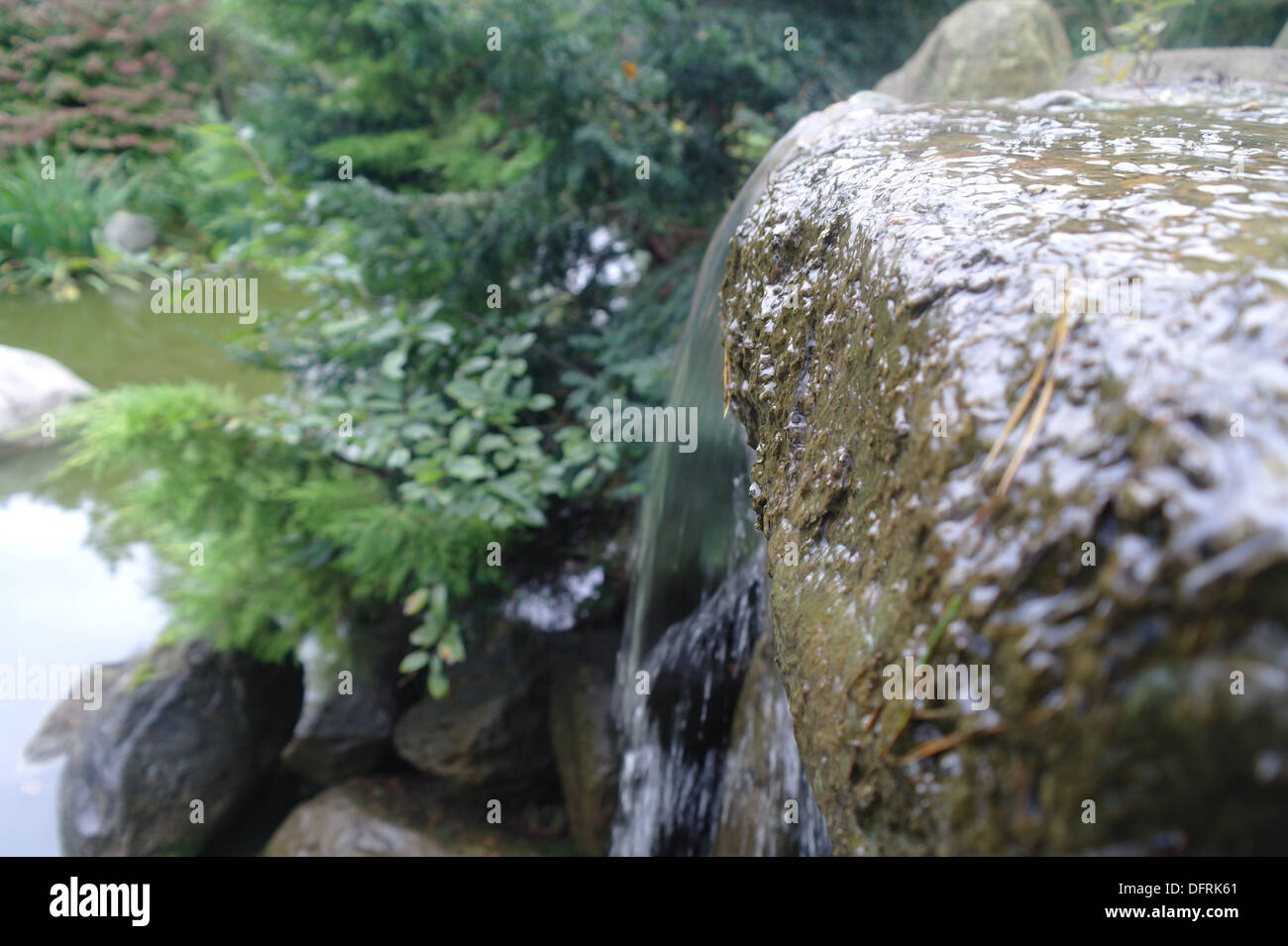 Water rushing off the side of a gleaming rock into a small lake. - Stock Image