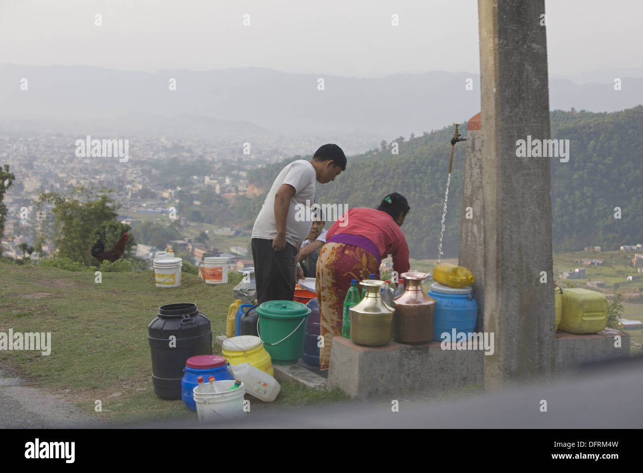 People filling and storing tap water. - Stock Image