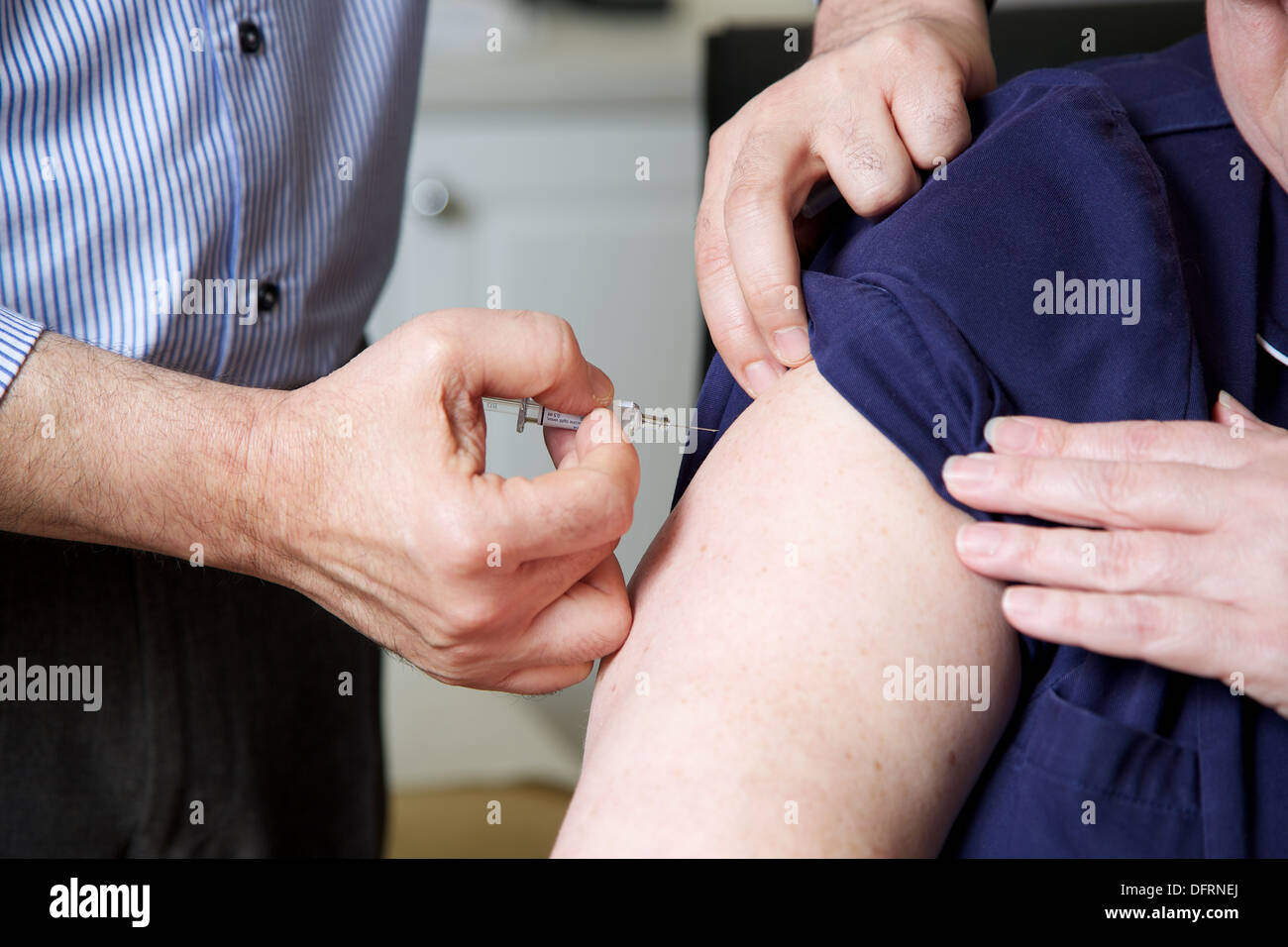 Doctor GP prepares to give the flu jab injection to a patient - Stock Image