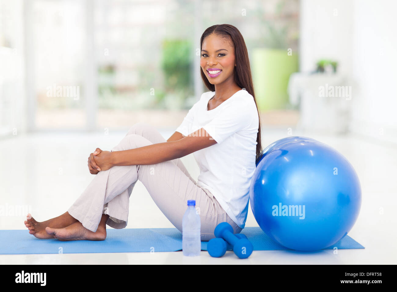 healthy afro American woman sitting on mat after working out - Stock Image