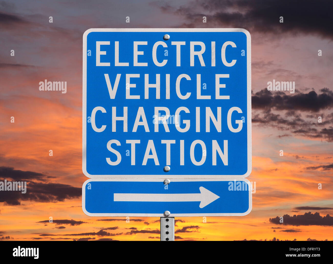 Electric vehicle charging station sign isolated with sunset sky. - Stock Image