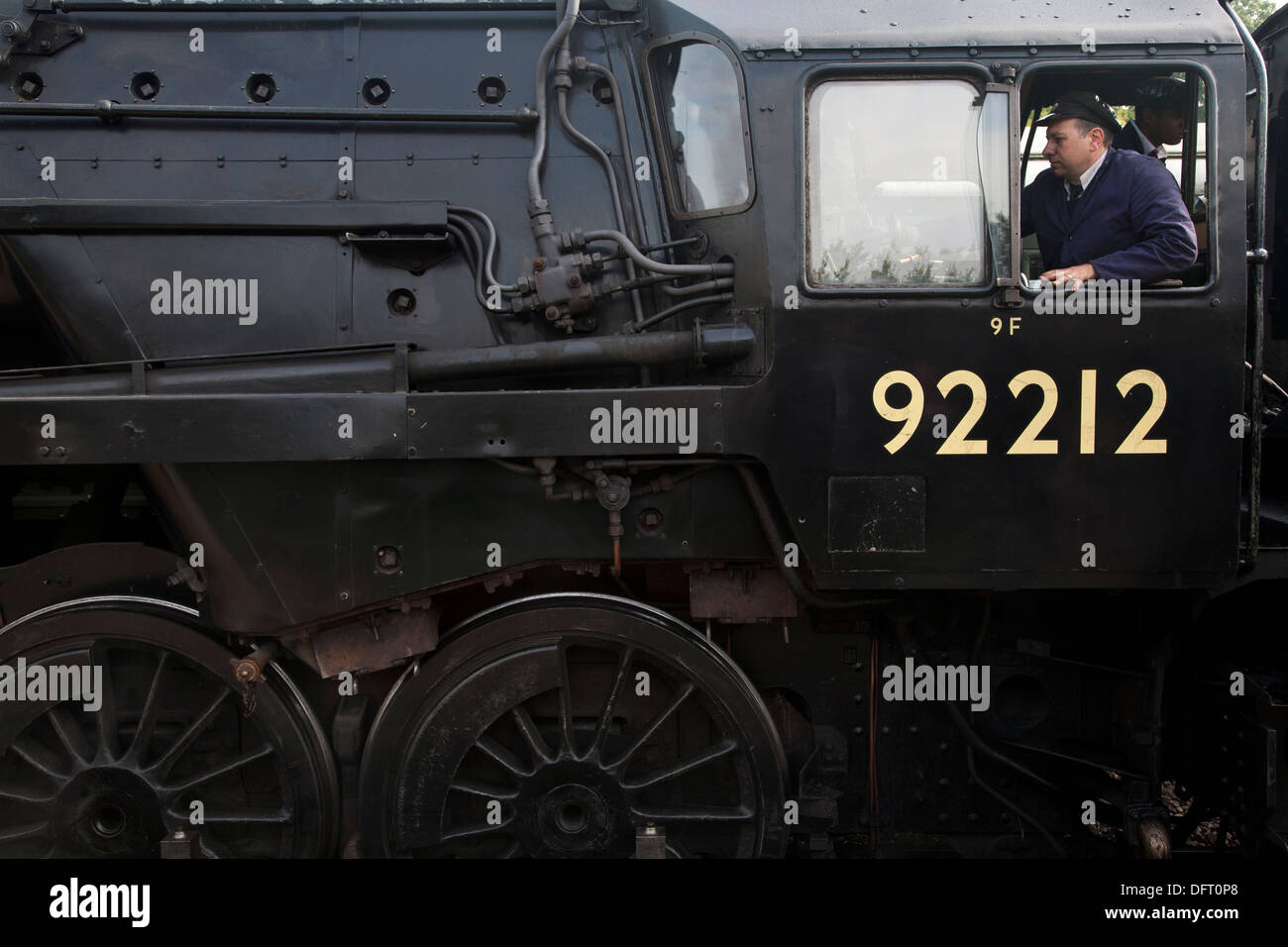 Steam locomotive 92212 with train driver in window on the Bluebell Railway - Stock Image