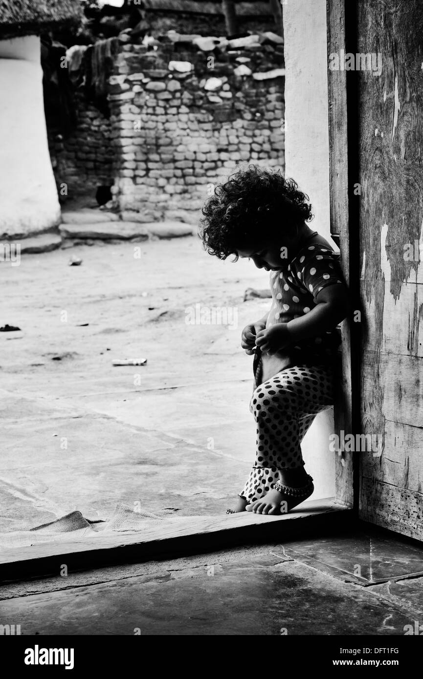Young indian girl standing at the doorway of her rural indian village house andhra pradesh